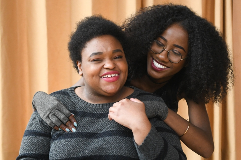 Close-up of two Black and disabled women smiling and holding hands - Disabled And Here